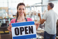 Pretty worker showing open sign Royalty Free Stock Images