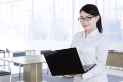 Pretty worker standing in office with laptop Stock Images