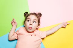 Pretty 4-year little girl with funny face on multicolor background. Bright colors and stylish picture stock image