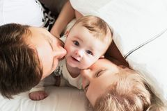 Pretty yong family in bed. Parents kissing their baby, top view stock photography