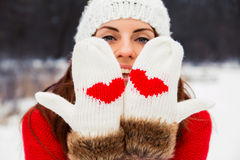 Pretty yong woman in mittens with hearts royalty free stock image