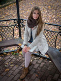 Pretty yong woman sitting in the arbor in autumn park.  Royalty Free Stock Photos
