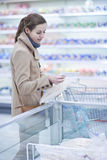 Pretty youman buying groceries in a supermarket Royalty Free Stock Images