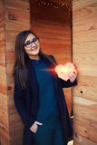 Pretty youn girl holding a heart-shaped gift for mom Stock Image