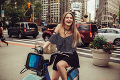 Pretty young adult woman enjoy the ride on rental bicycle in New York City. Stock Photo