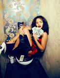 Pretty young african american woman in luxury restroom with mone Stock Photo
