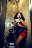 Pretty young african american woman in luxury restroom with money, like prostitute