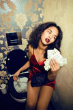 Pretty young african american woman in luxury restroom with money, like prostitute. Dirty cash concept Royalty Free Stock Photos