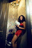 Pretty young african american woman in luxury restroom with money, like prostitute. Dirty cash concept Stock Image