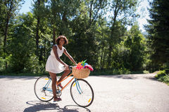 Pretty young african american woman riding a bike in forest Royalty Free Stock Images