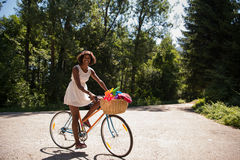 Pretty young african american woman riding a bike in forest Stock Photos