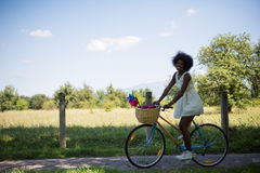 Pretty young african american woman riding a bike in forest Stock Photo