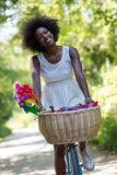 Pretty young african american woman riding a bike in forest Stock Photography