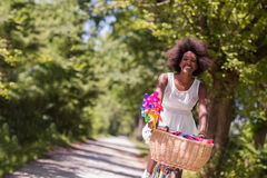 Pretty young african american woman riding a bike in forest Royalty Free Stock Photography