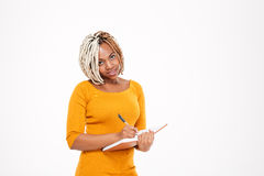 Pretty young african american woman standing and writing in notebook Stock Images