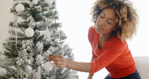 Pretty young African woman decorating an Xmas tree Stock Images