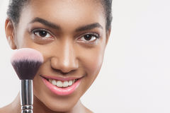 Pretty young african woman is doing facial make-up stock photos