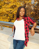 Pretty young african woman wearing a red checkered shirt in evening Stock Images