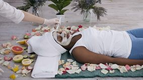 Pretty young afro american woman resting with closed eyes in beauty centre with closed eyes while cosmetologist applying. Facial mask . Woman cosmetologist stock video footage