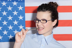 Pretty young American woman is ready to study. Waist up portrait of attractive smart girl standing near the USA flag. She is standing and raising a pen to her Stock Photography