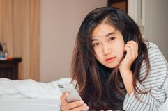 Pretty young Asia woman holding and looking at camera on the bed. Pretty young Asia woman holding smart phone and looking at camera on the bed Stock Image