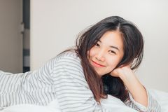 Pretty young Asia woman smiling and looking at camera. On the bed Stock Photography