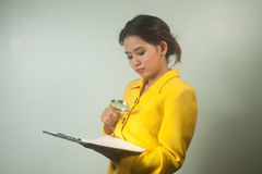 Pretty young Asian business woman looking document by magnifying Stock Images