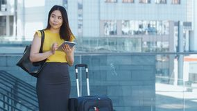 Asian female using touchpad during business travel. Pretty young asian female using touchpad during business travel on business center background outdoors stock video footage