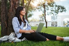 Pretty young asian student sitting on grass under the tree holdi Royalty Free Stock Image