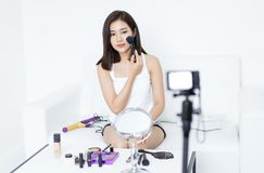 Pretty young Asian woman blogger using brush for make up applying. Process of making a video about make-up beauty for her blog on. Living room royalty free stock image