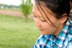 Pretty Young Asian Woman, Copy Space. Portrait of a pretty young Korean American woman in her twenties at a park.  She is in deep thought Royalty Free Stock Images