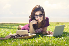 Pretty young asian woman is dreaming with a laptop lying on the Stock Photos