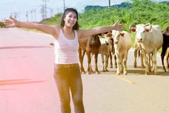 Pretty young Asian woman enjoy summer day with cow on a road. Royalty Free Stock Photo