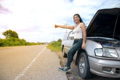 Pretty young Asian woman with hand up calling passing car. stock image