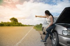 Pretty young Asian woman with hand up calling passing car. stock images
