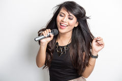 Pretty young asian woman happy singing a song. Portrait of pretty young asian woman singing karaoke with a mike royalty free stock photography