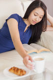 Pretty young asian woman lying on the sofa reading a book reaching for her coffee Stock Images