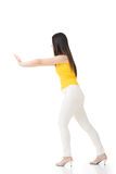 Pretty young asian woman pushing or leaning on wall. Royalty Free Stock Images