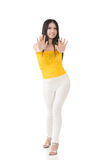 Pretty young asian woman pushing or leaning on wall. Royalty Free Stock Image