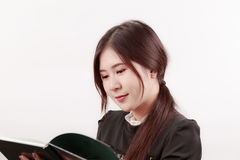 Pretty young Asian woman reading a book with considerate and thoughtful posture. Royalty Free Stock Photography