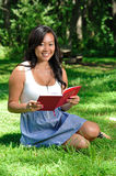 Pretty young Asian woman reading in park Stock Photo