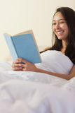 Pretty young asian woman sitting in bed reading a book Stock Photo