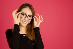 Pretty young asian woman in the studio. With pink background royalty free stock photo