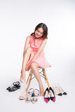Pretty young asian woman trying on a few pairs of high heels Royalty Free Stock Photo