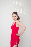 Pretty young asian woman wearing red dress with balloons in hand Royalty Free Stock Photo
