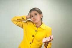 Pretty young Asian woman in yellow suit use calculator. Stock Photo