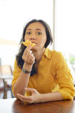 Pretty Young Attractive Woman Eating Donut  At Cafe Royalty Free Stock Photos