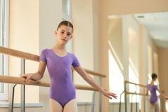 Pretty young ballerina near barre. Beautiful young girl standing near railing at ballet hall and looking at camera. Lovely young ballet-dancer Royalty Free Stock Photography
