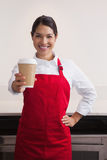 Pretty young barista offering cup of coffee to go Royalty Free Stock Images