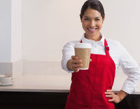 Pretty young barista offering cup of coffee to go smiling at camera